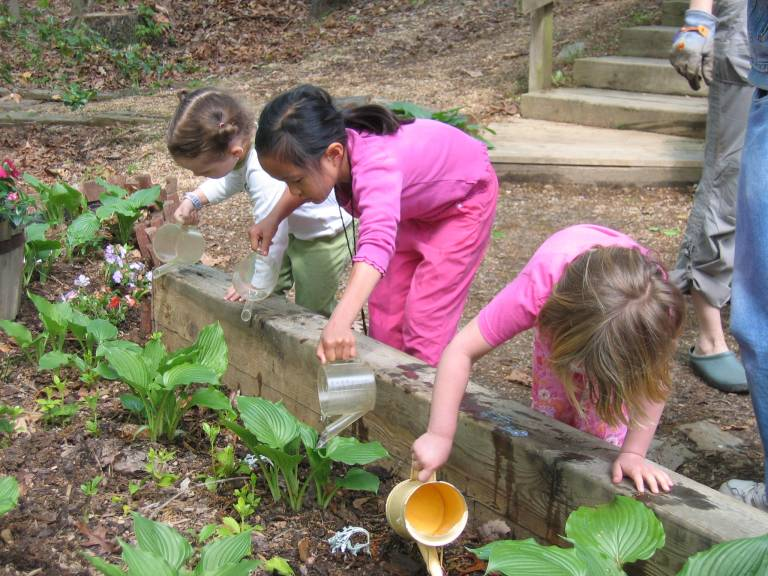 Children watering the plants in the natural play space