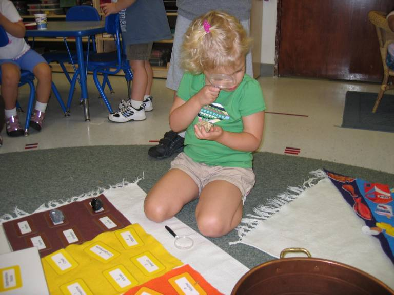 Child using a magnifying glass Montessori school reston
