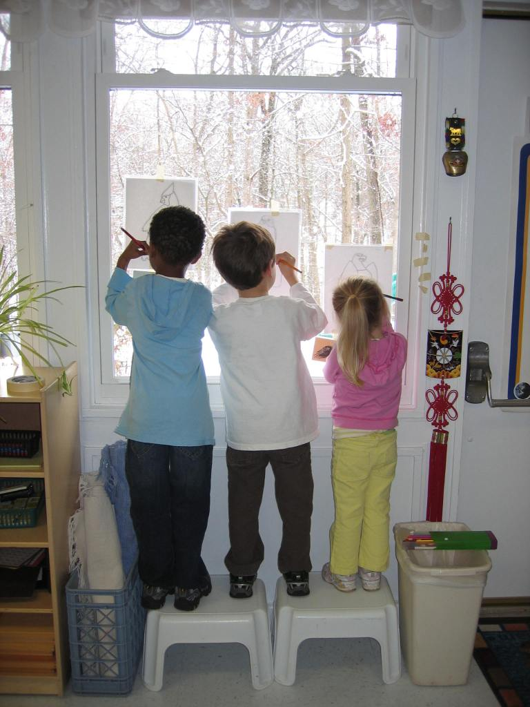 3 children working at a window in a Montessori mixed-age classroom