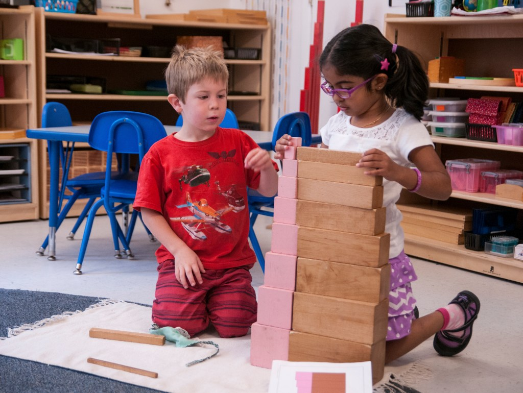 Two children work with the sensorial materials at Children's House Montessori School of Reston
