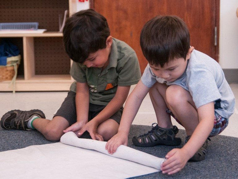 Two boys practicing helpfulness / teaching character development in early childhood