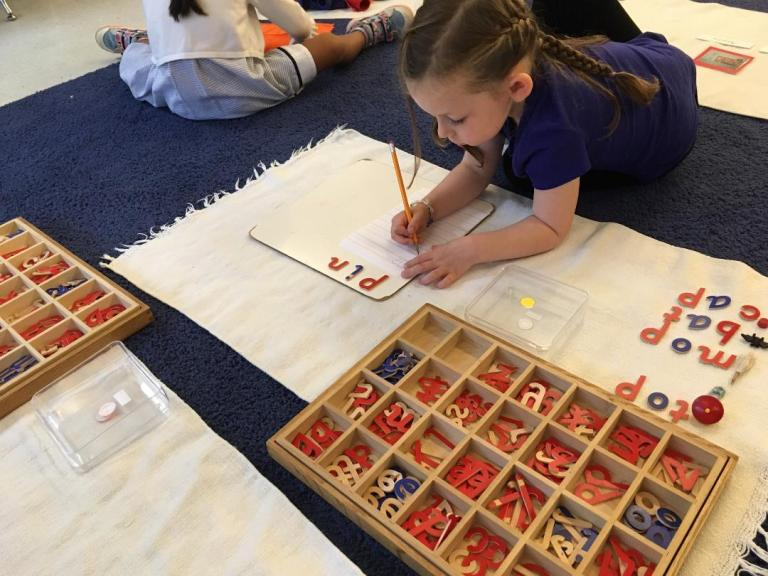 A child writes words with the Moveable Alphabet. Difference between Montessori and Traditional Preschool.