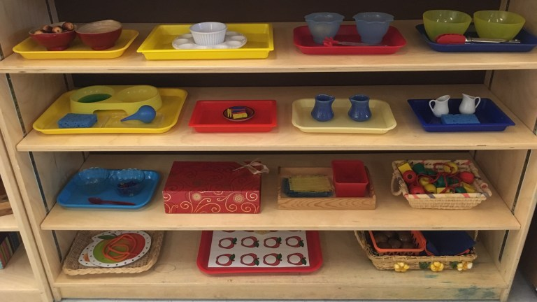 A shelf in a Montessori classroom. How do Montessori schools teach independence?