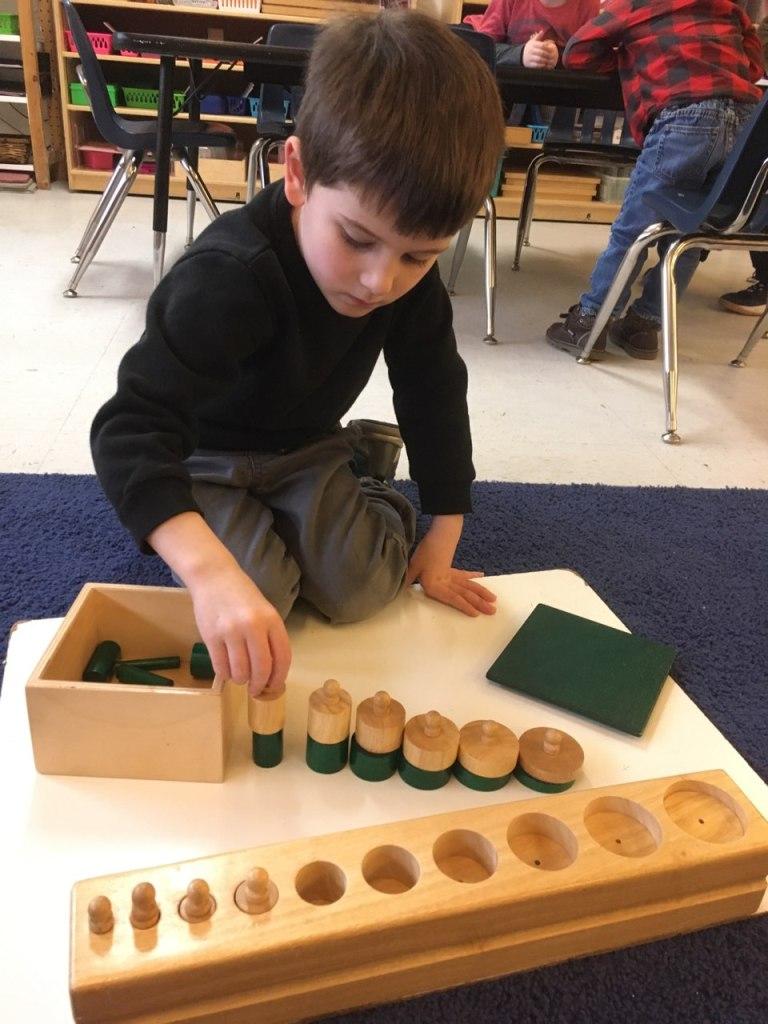 Child working with Montessori Sensorial materials.