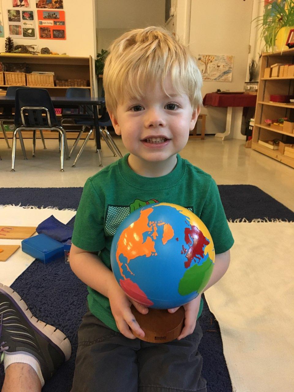 Boy holding Montessori globe.