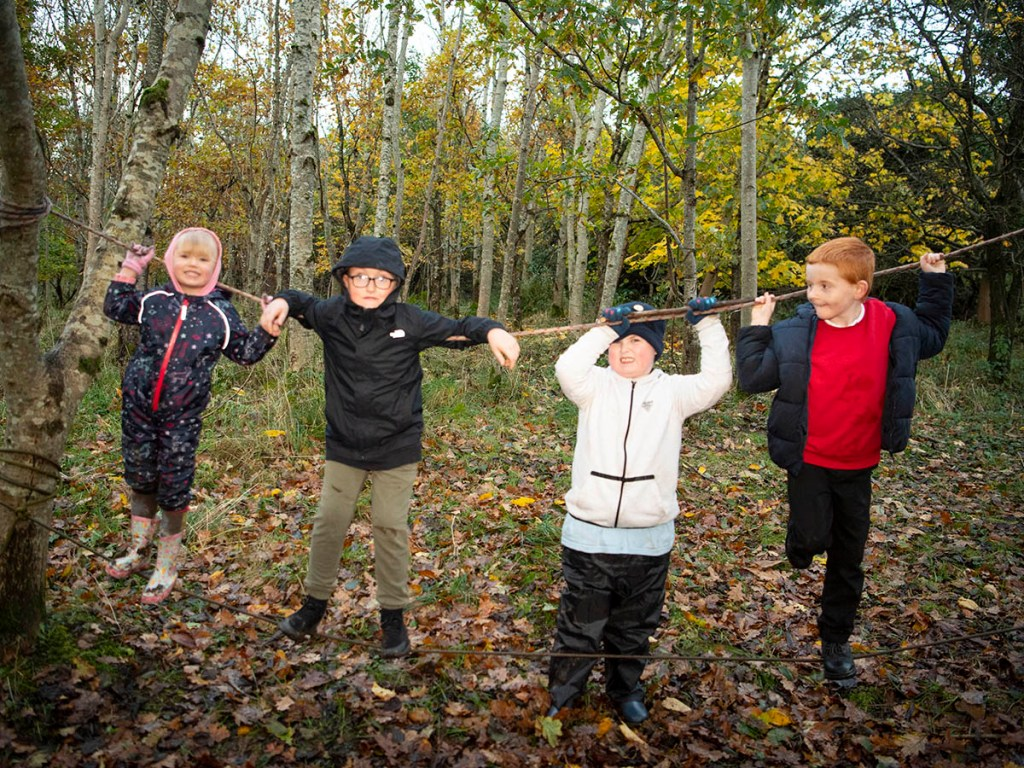 Four children playing in a woodland