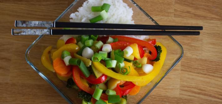 Ein süßscharfer Gemüsewok mit Reis und Esstäbchen mit verschiedenem Gemüse