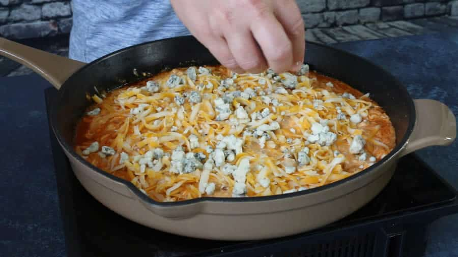 Sprinkle on the cheddar cheese and blue cheese evenly over the top, like so.