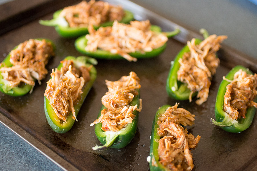 Stuff the jalapeno slices with shredded chicken.