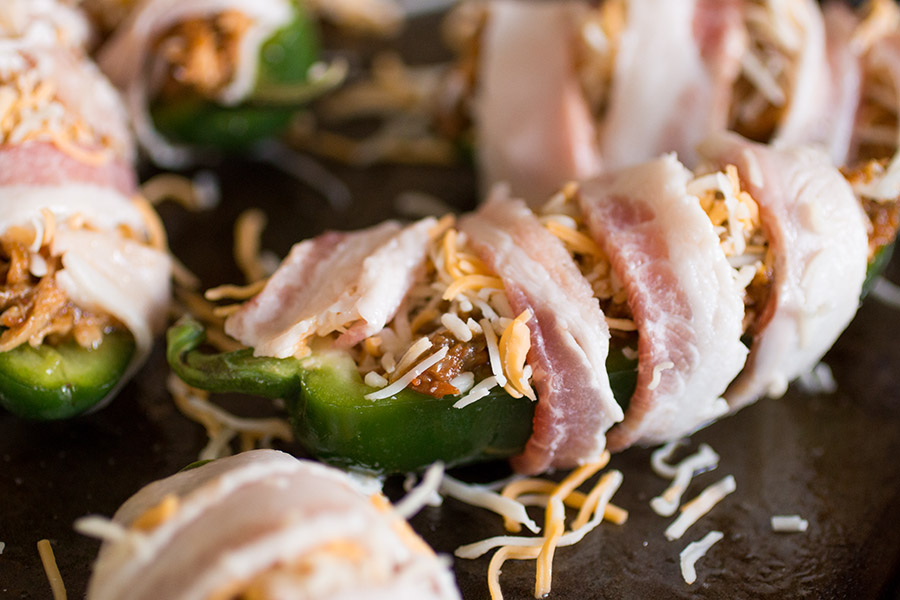 Gently wrap your jalapeno poppers in bacon, like this , then bake them.