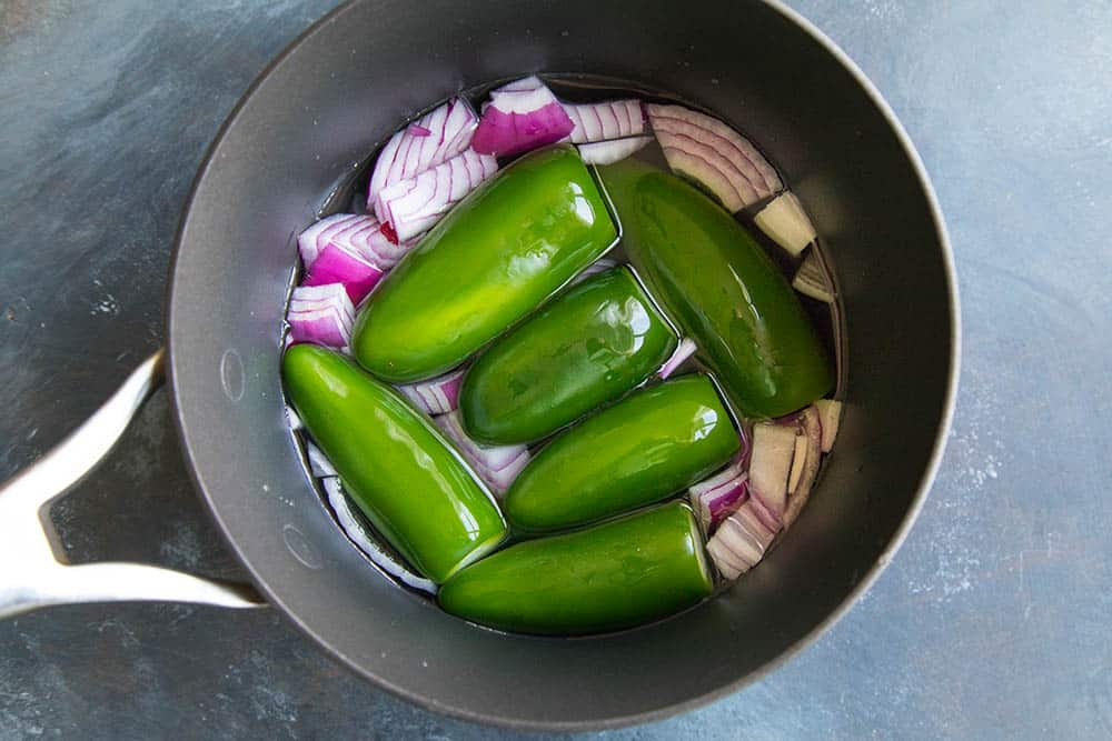 Boiling jalapenos and onions to make our creamy jalapeno sauce