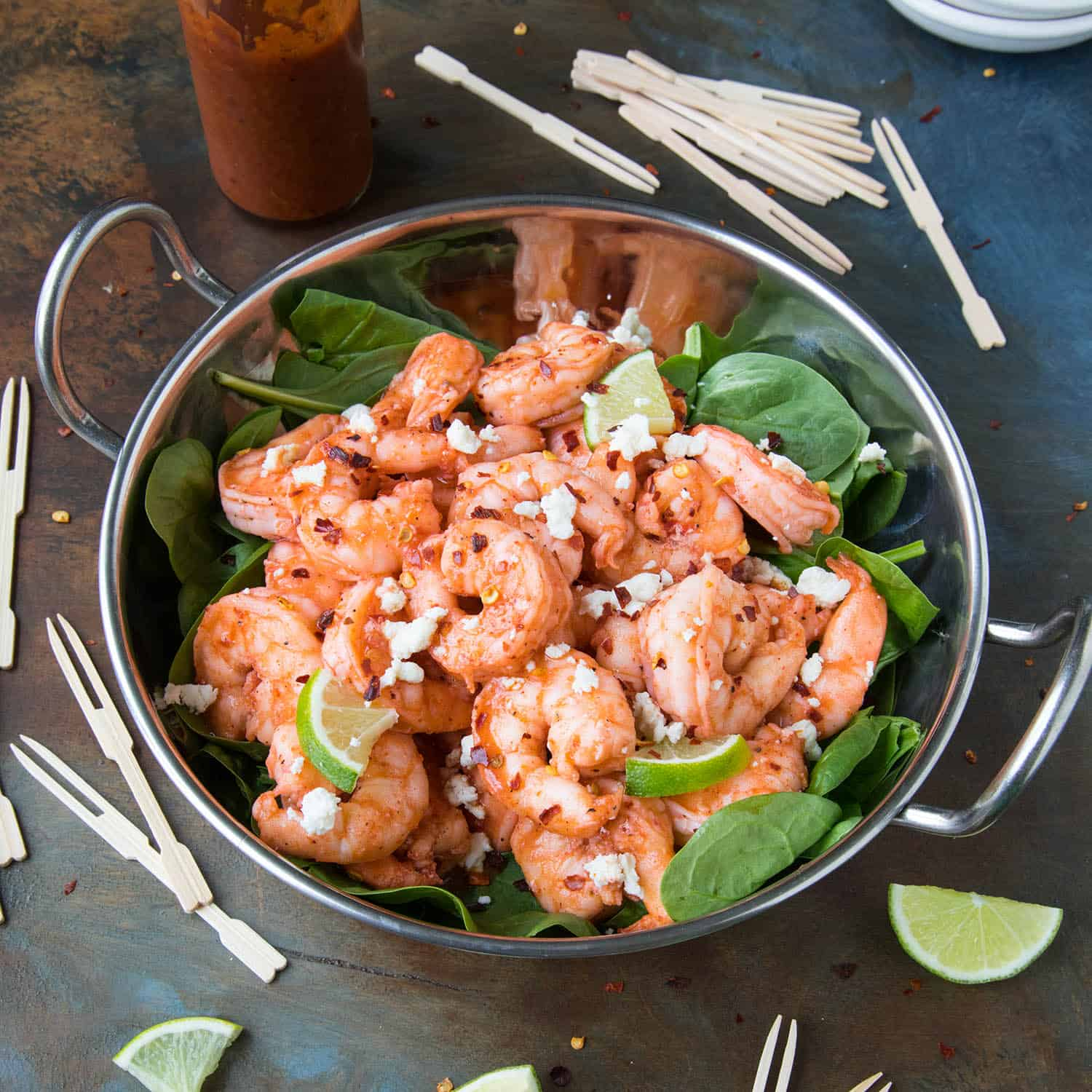 Grilled Buffalo Shrimp in a bowl over spinach leaves - they satisfy everyone.