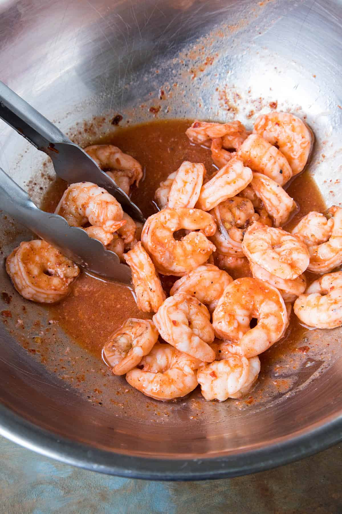 Tossing the shrimp in homemade Buffalo sauce