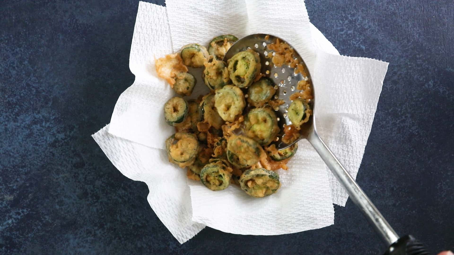 Drain the fried jalapeno peppers on paper towels