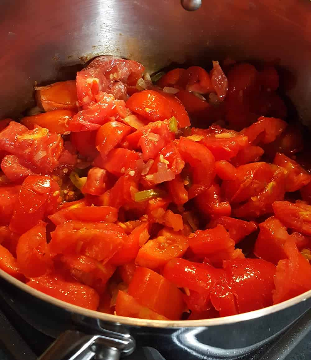 Adding the tomatoes to a pot