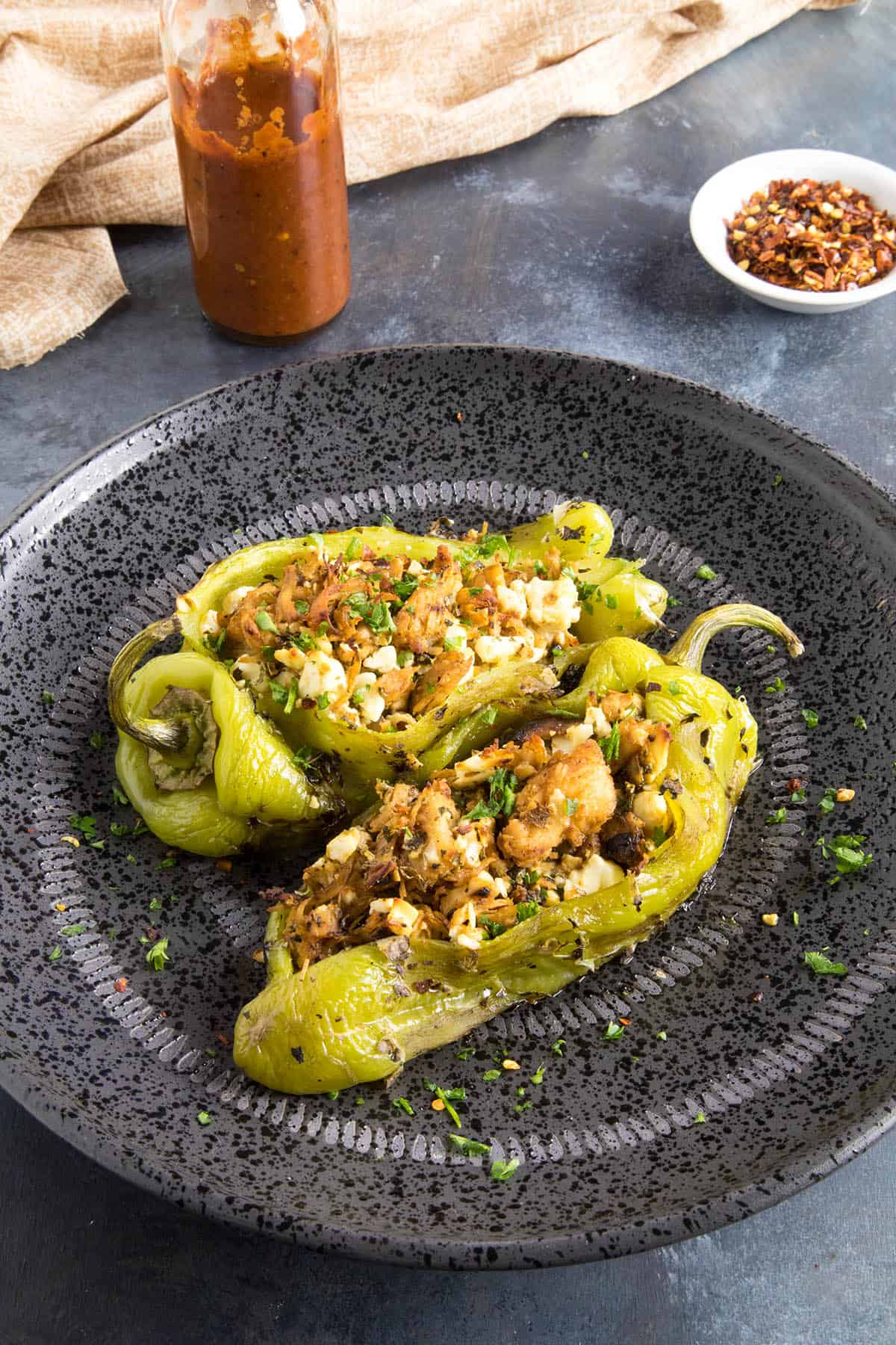 Chicken and Cheese Stuffed Anaheim Peppers - Served up on a plate with hot sauce on the side