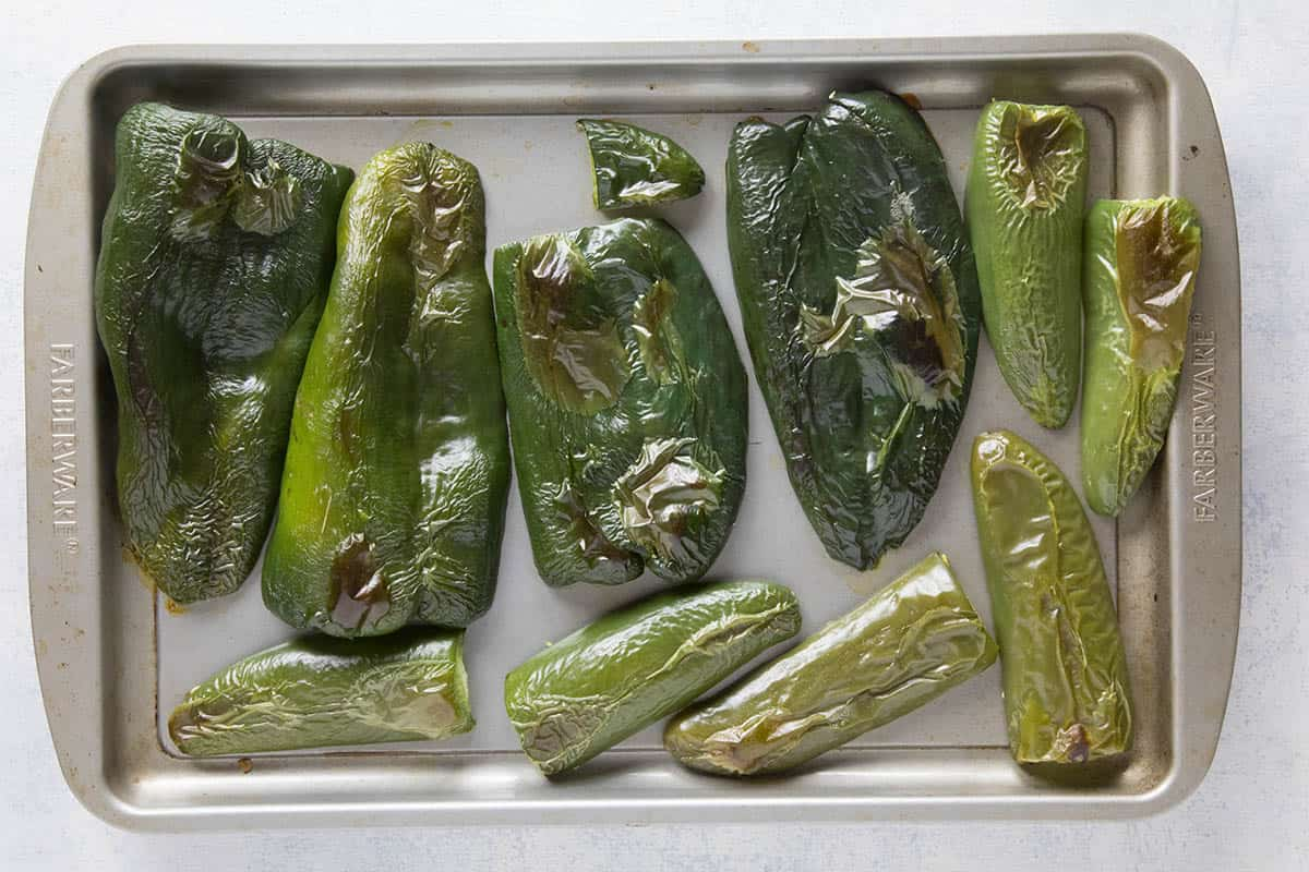 Poblano peppers and jalapeno peppers, sliced and on a baking sheet, roasted