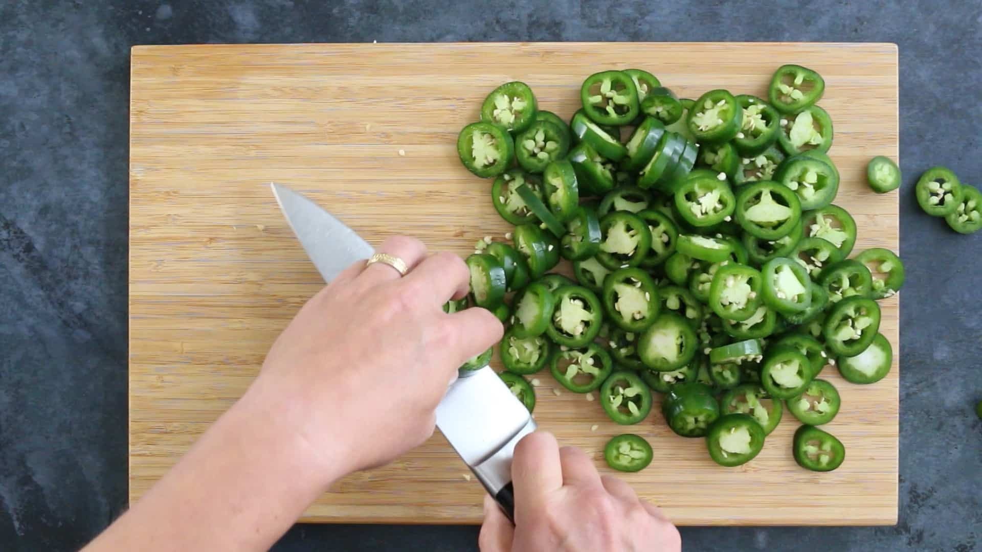 Chopping jalapeno peppers in a pan to make Candied Jalapenos (Cowboy Candy)