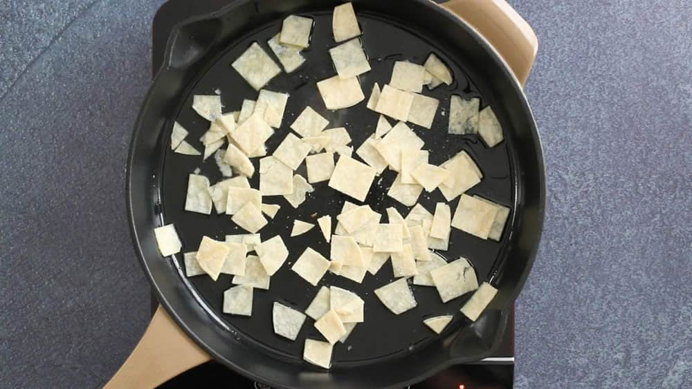 Frying tortilla strips in a pan