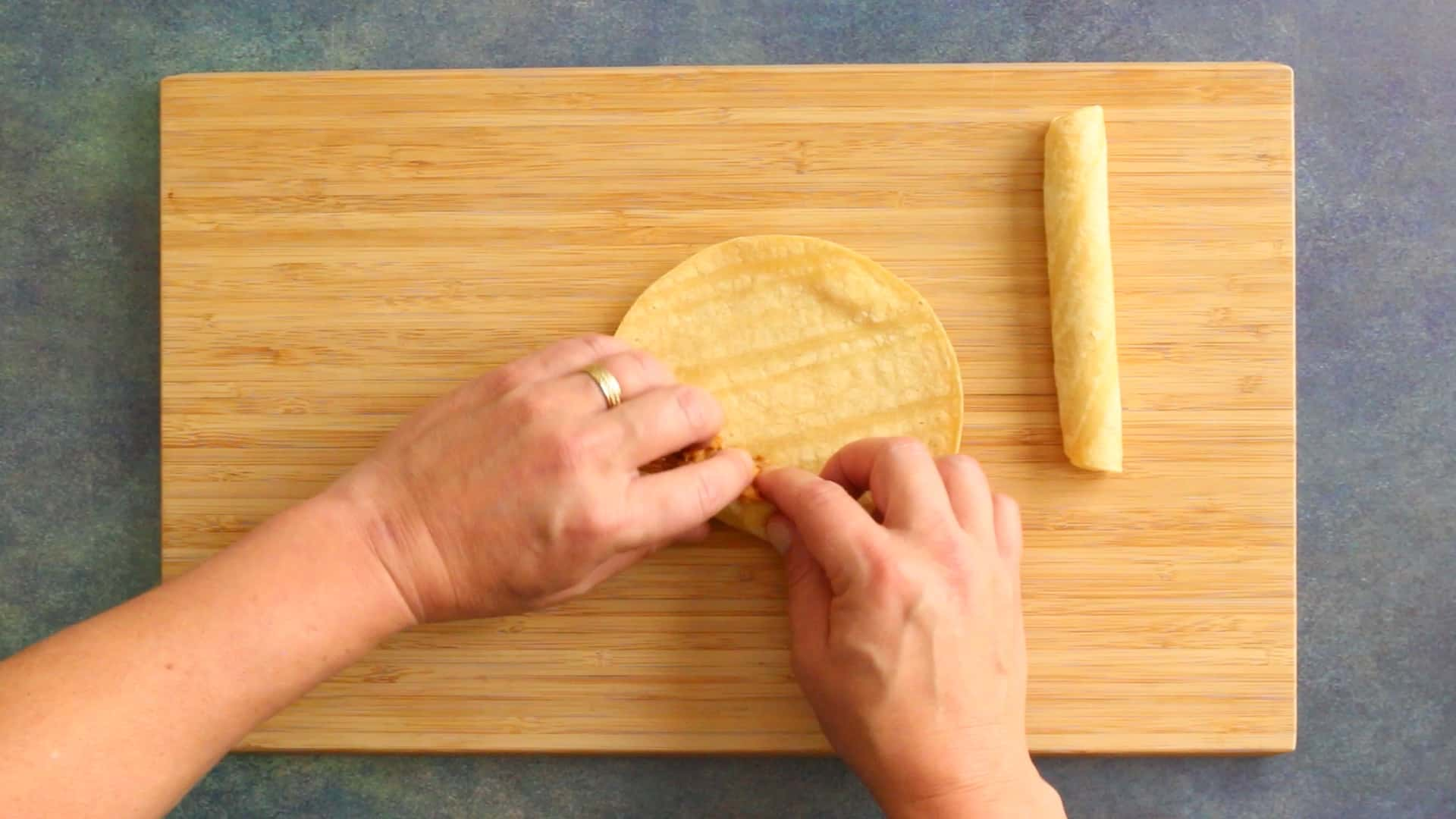 Rolling a chicken taquito in a softened corn tortilla