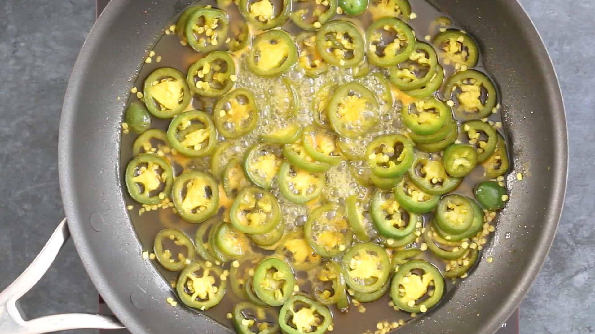 Simmering jalapeno peppers in a pan to make Candied Jalapenos (Cowboy Candy)