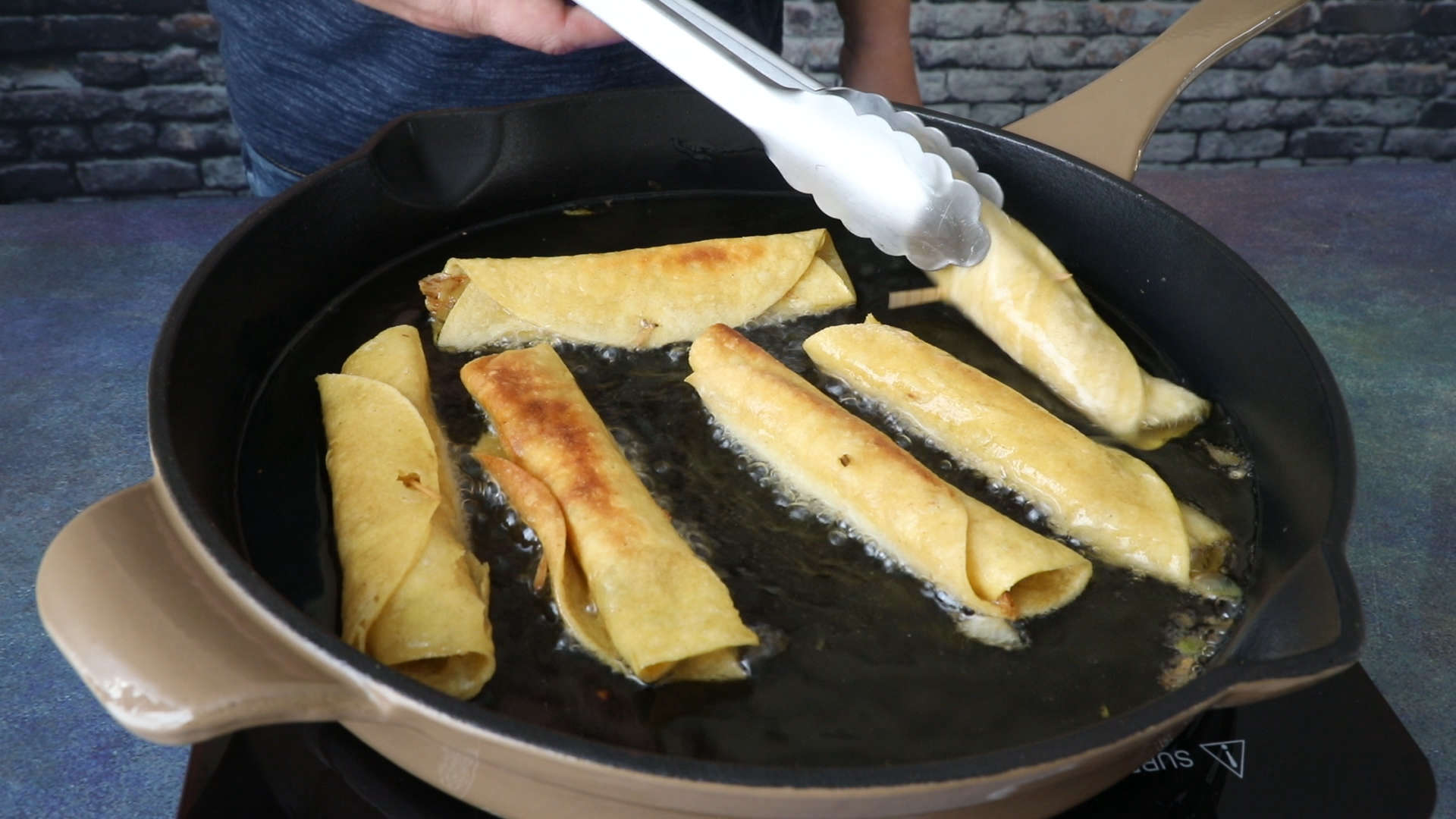 Frying the Chicken Taquitos in oil in a pan