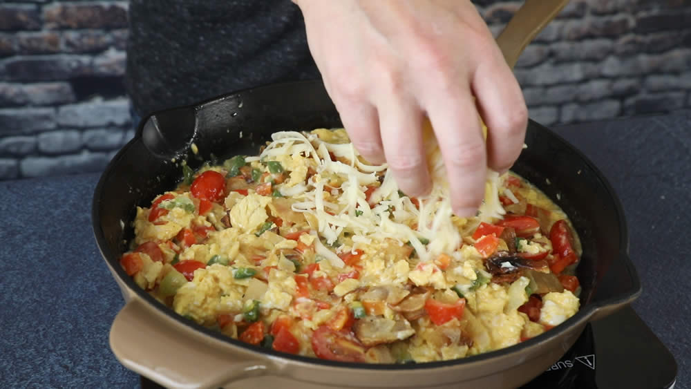 Adding cheese to our Migas dish