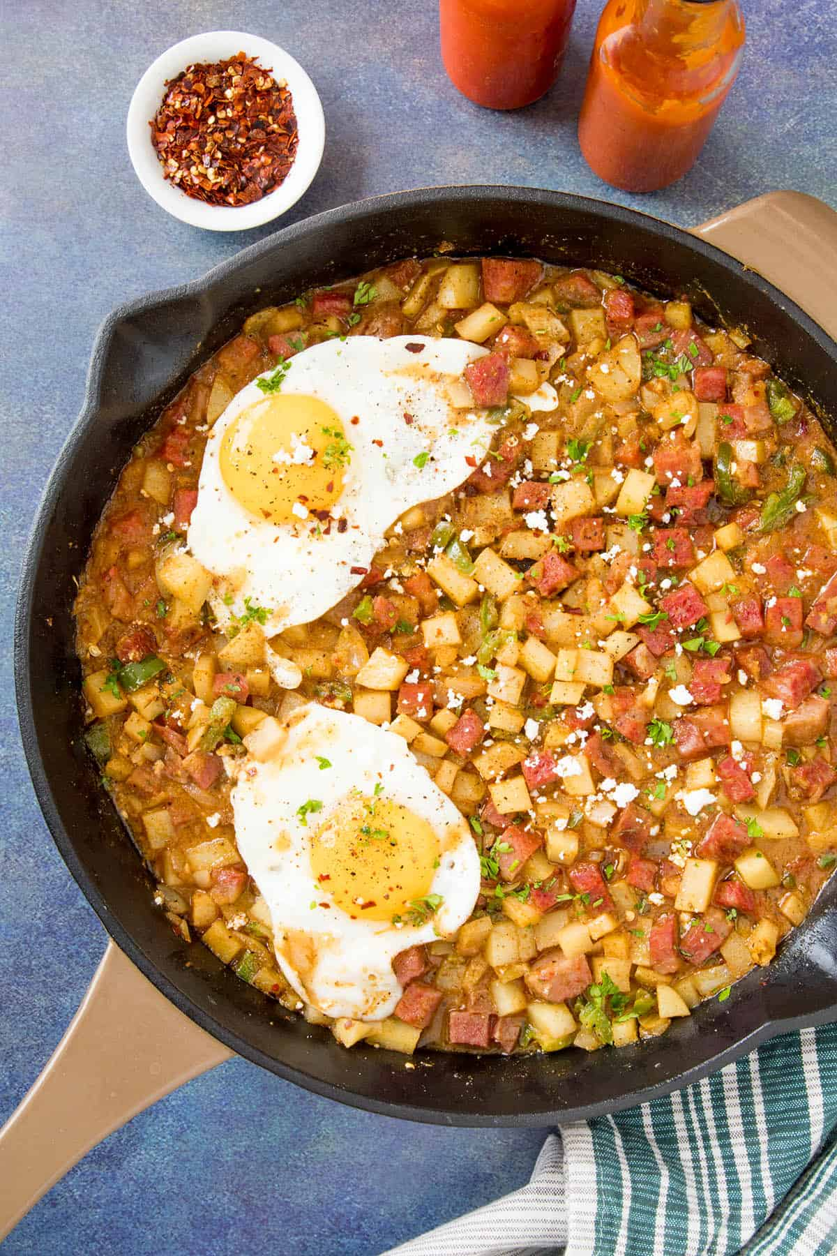 Corned Beef Hash Recipe – Madness Style, in a pan, ready to serve, with fried eggs on top