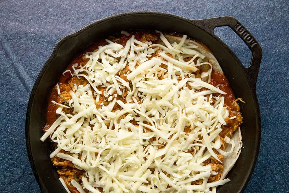 Lots of cheese layered over corn tortillas and chipotle chicken in a pan