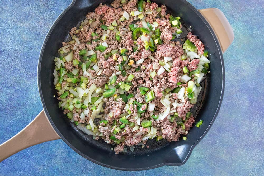 Cook down the ground beef and chicken livers with peppers, onion and celery