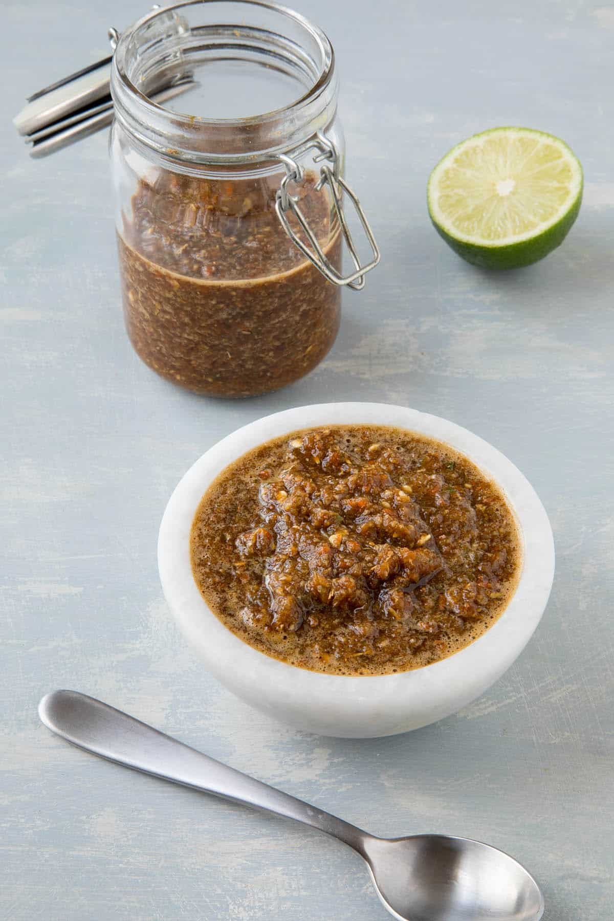 This Jamaican jerk sauce is in a bowl with some extra in a container, luxurious and spicy