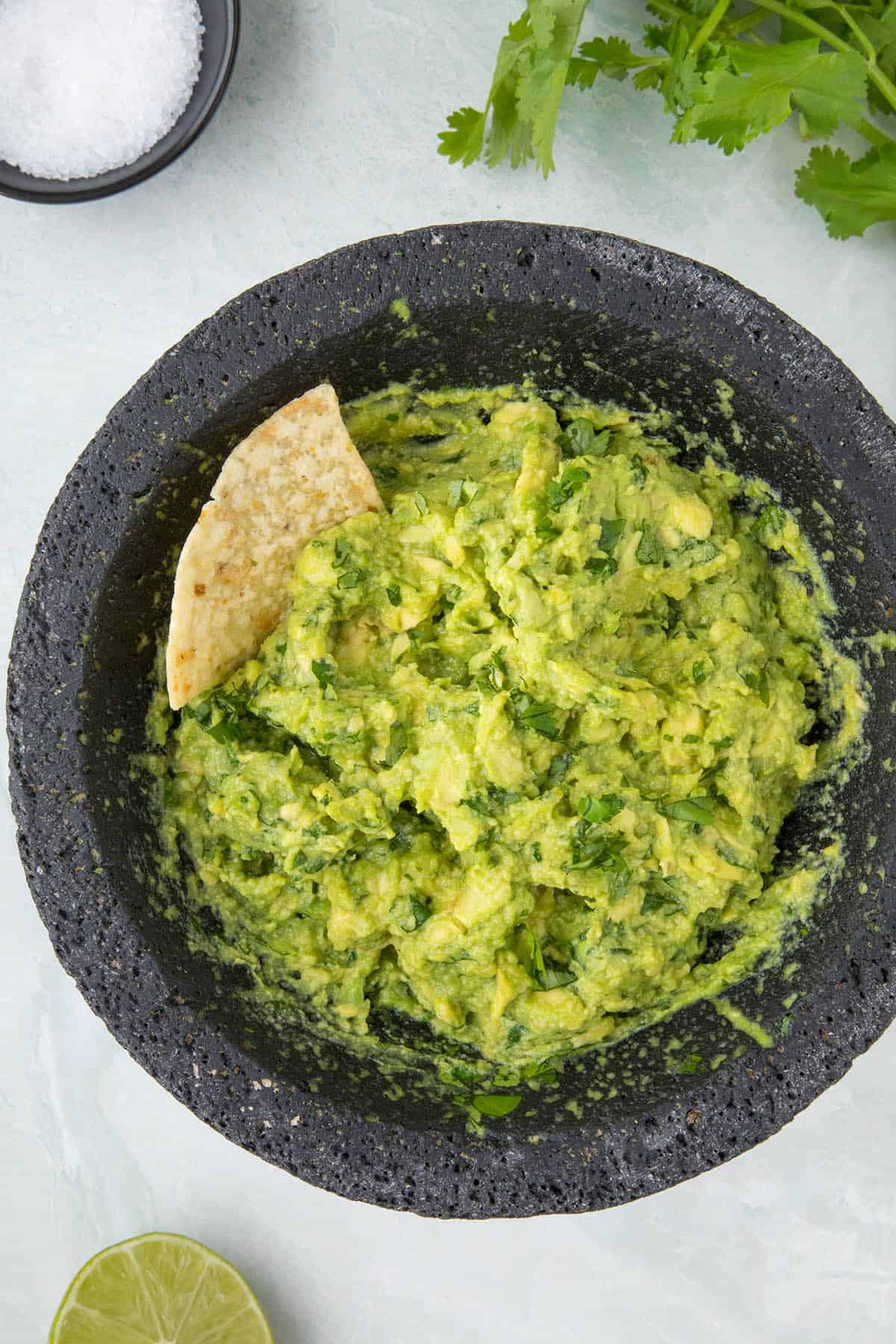 Fresh guacamole in a bowl with a chip