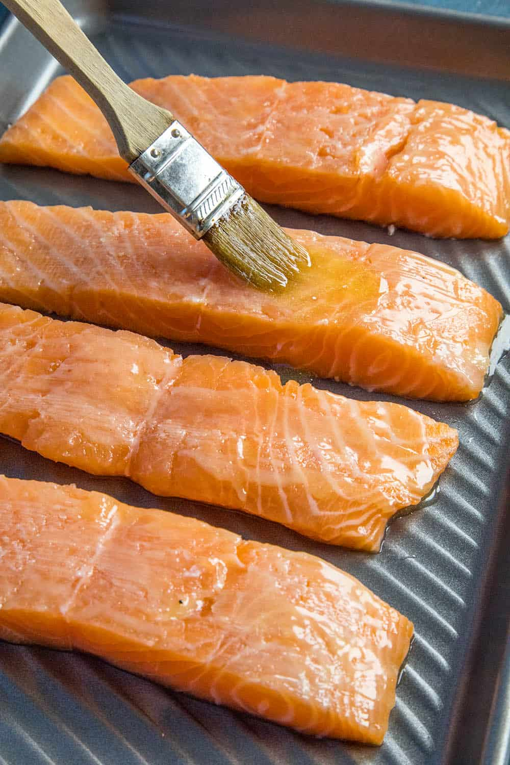 Buttering the salmon before seasoning them