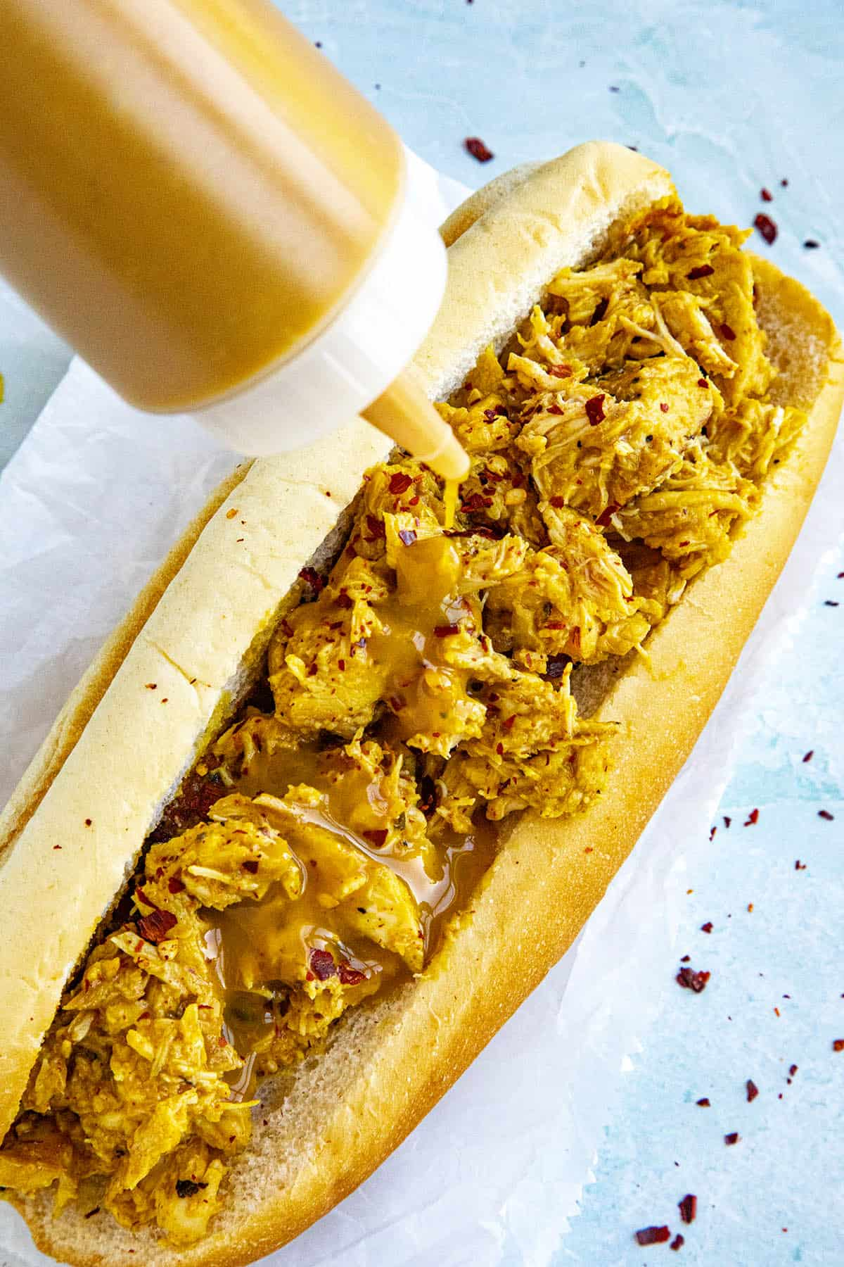 Carolina Mustard BBQ Sauce being squirted onto a pulled chicken sandwich