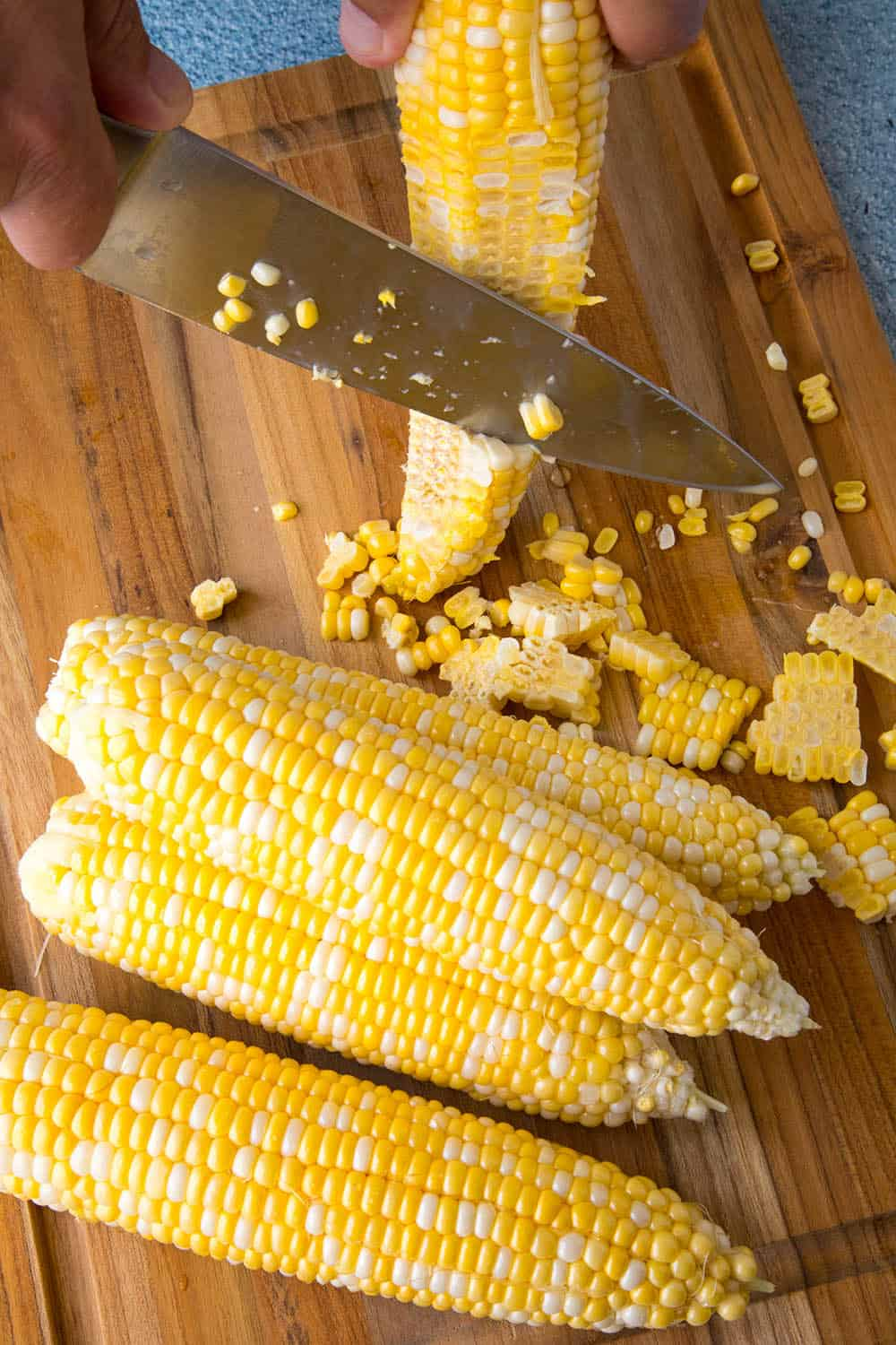 Cutting corn kernels from the corn cobs