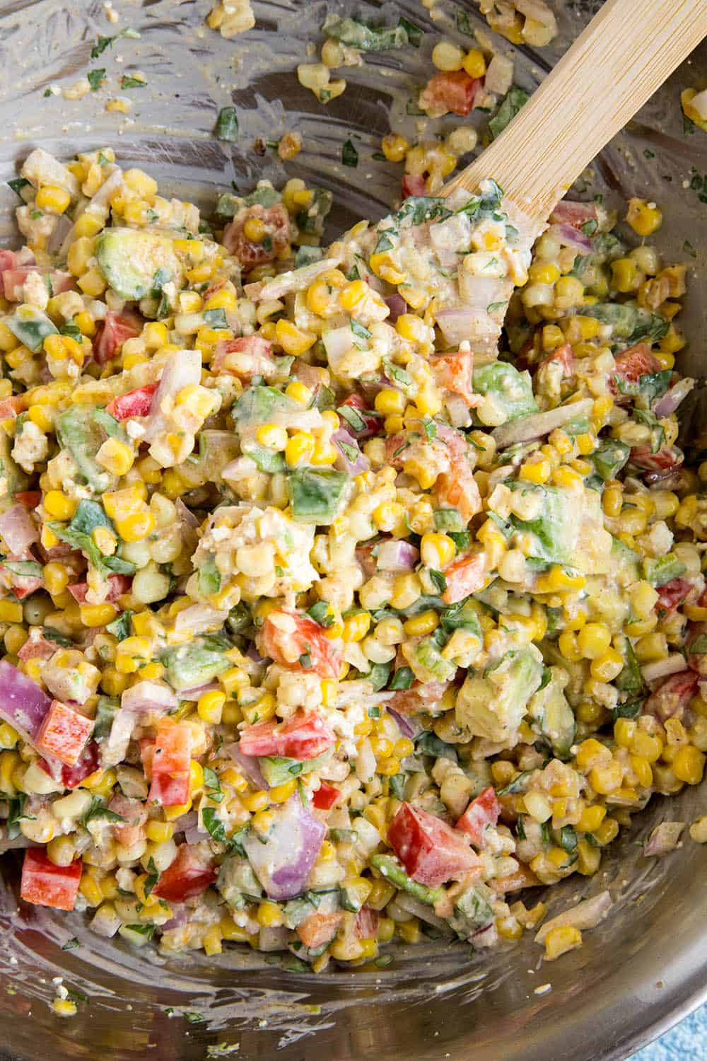 Mixing the elotes salad ingredients