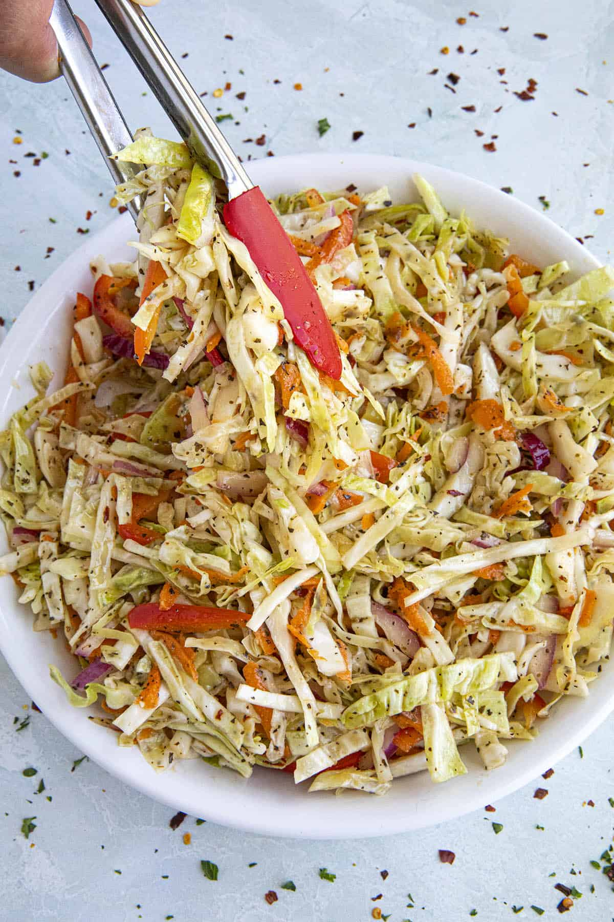 Mike scooping up Vinegar Coleslaw with tongs