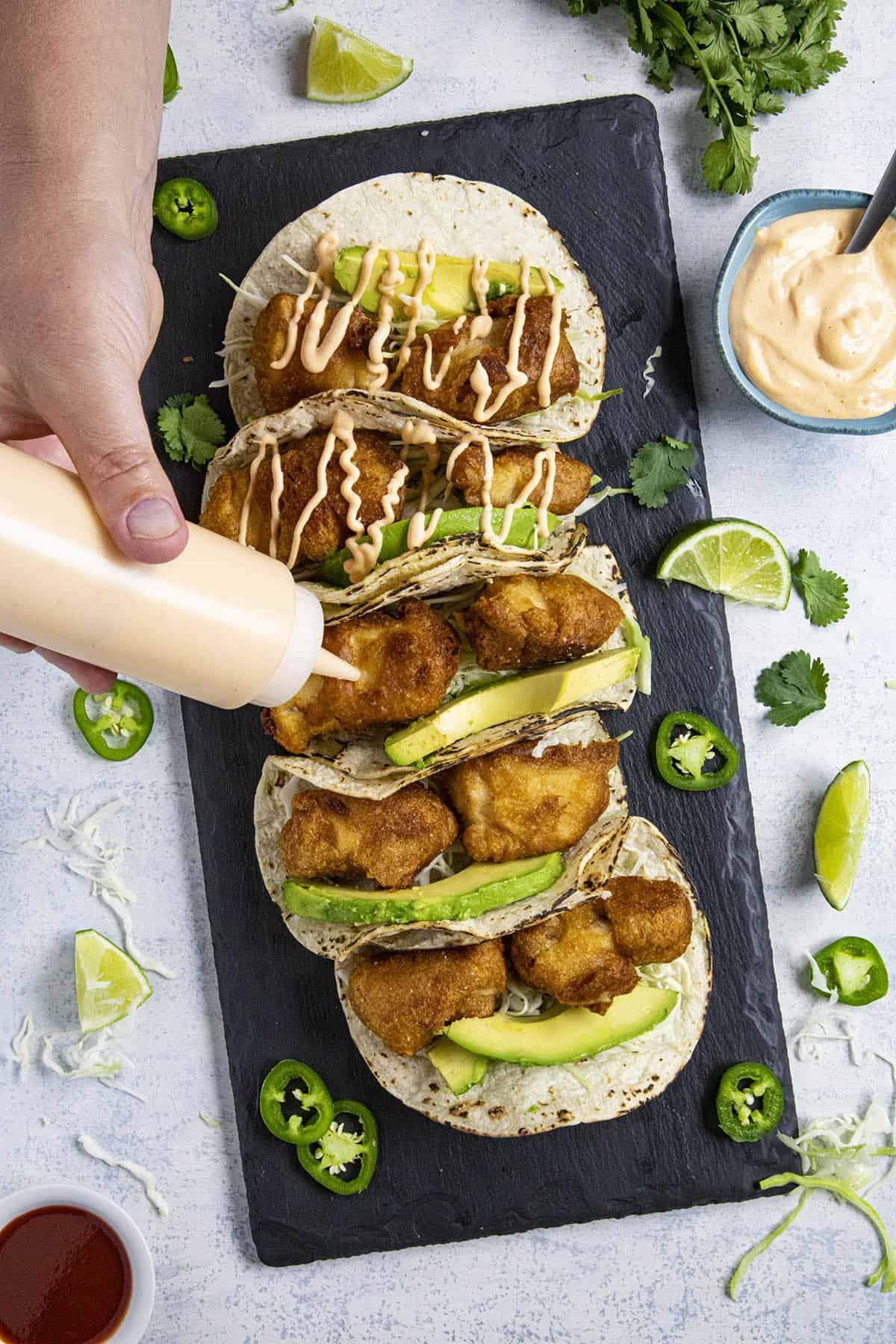Adding sauce to our baja fish tacos