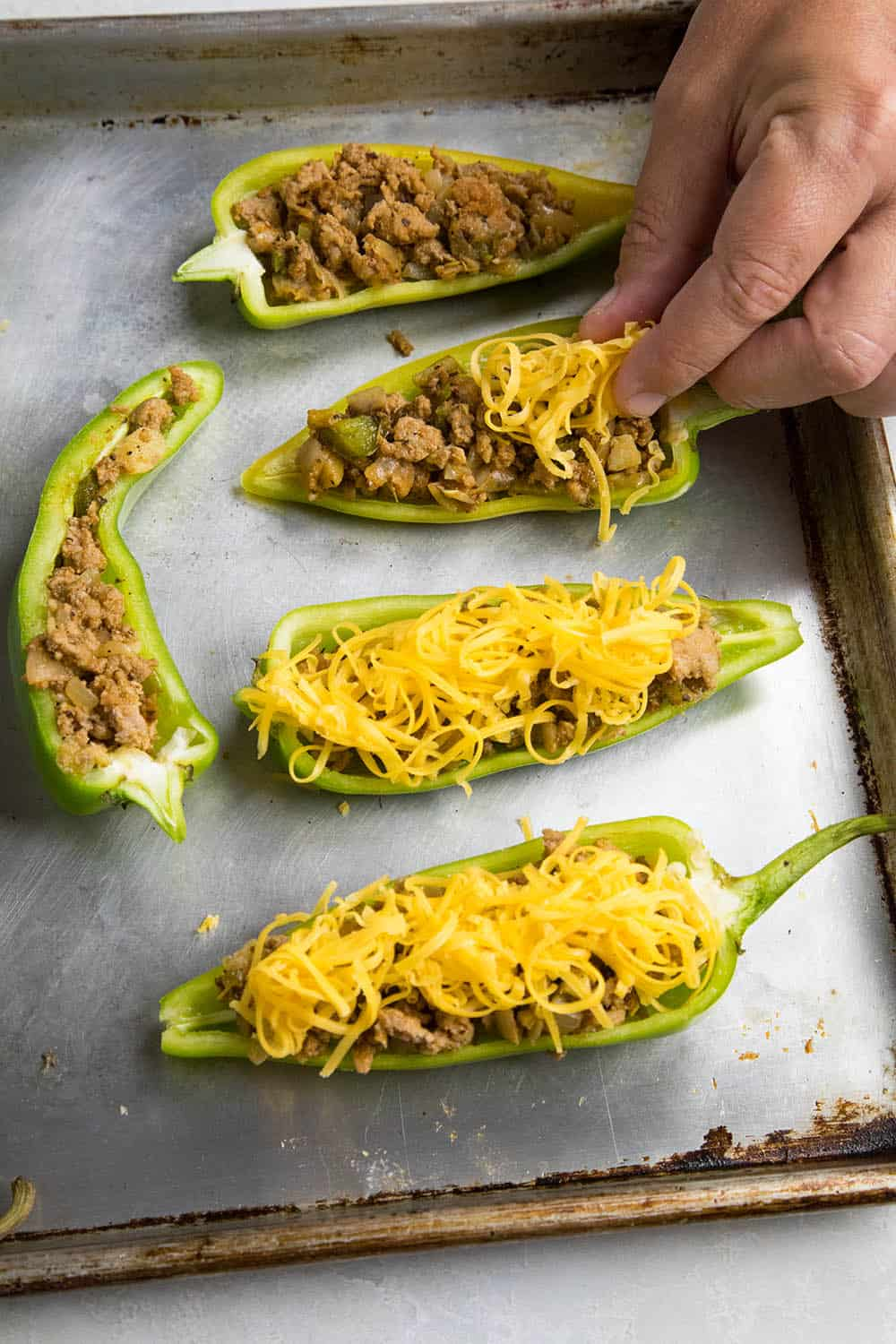 Topping the stuffed Anaheim peppers with cheese
