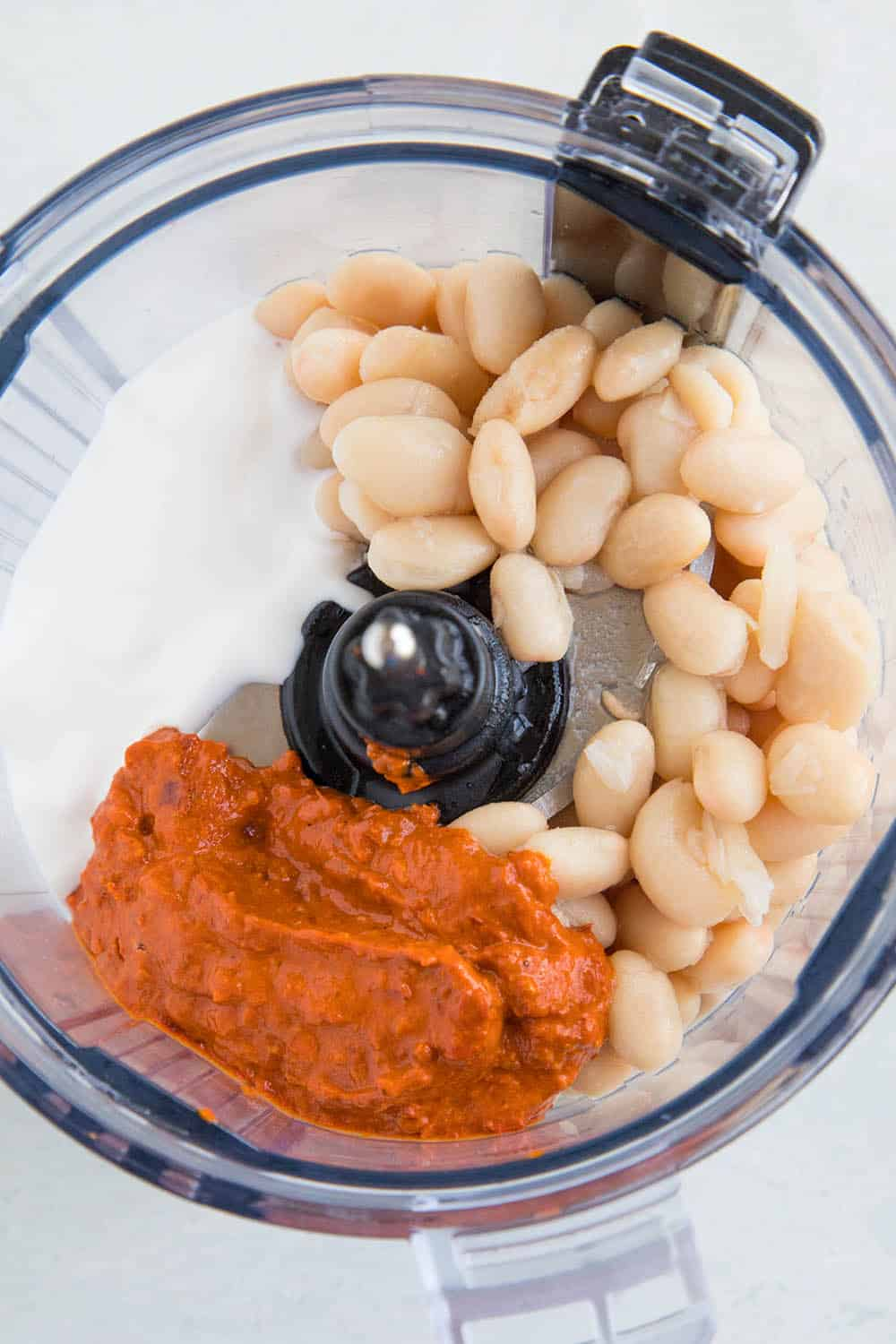 Ingredients for my Creamy White Bean Dip with Harissa recipe in a food processor