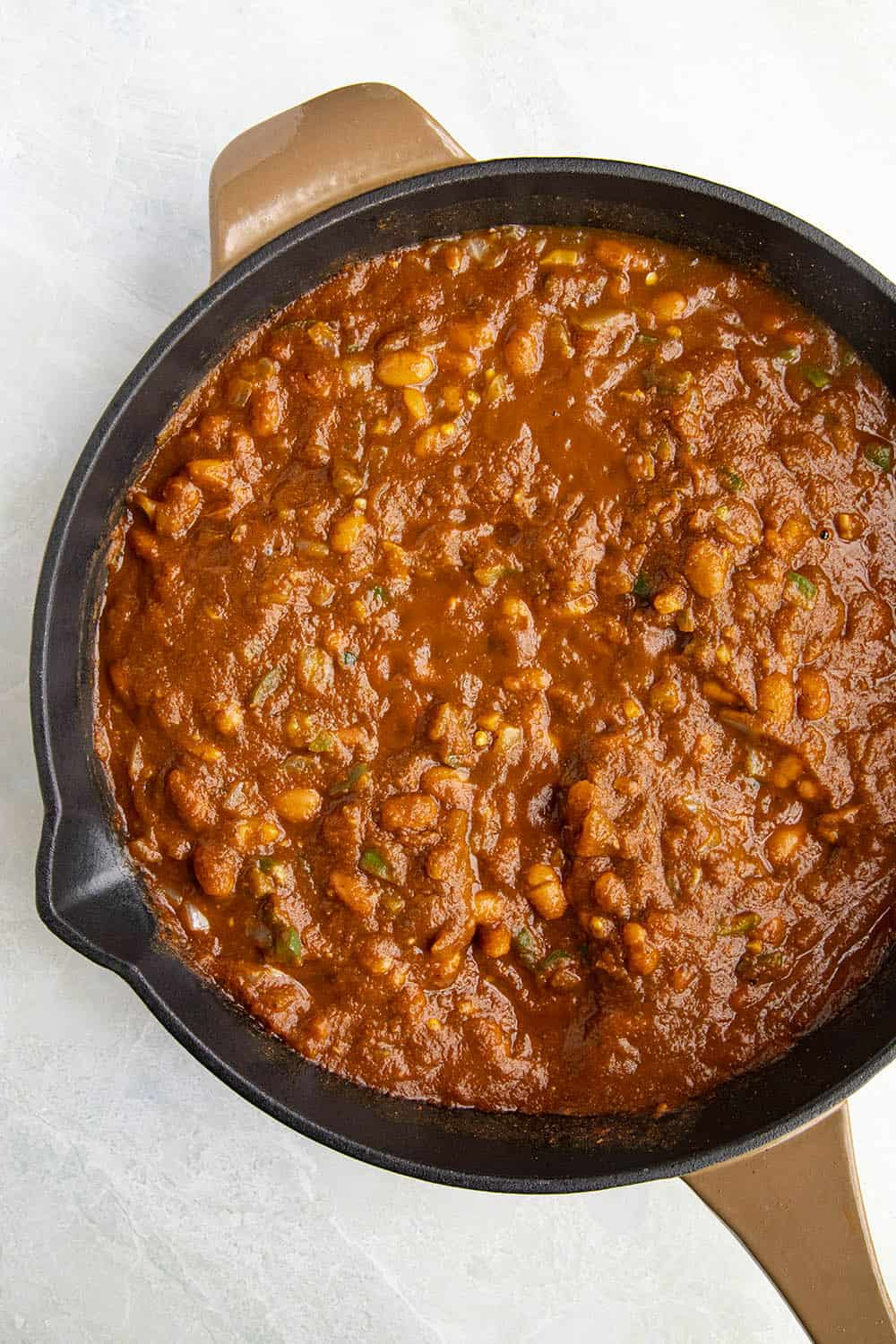 Cooking down the ranchero sauce and beans to make Huevos Ranchers Casserole