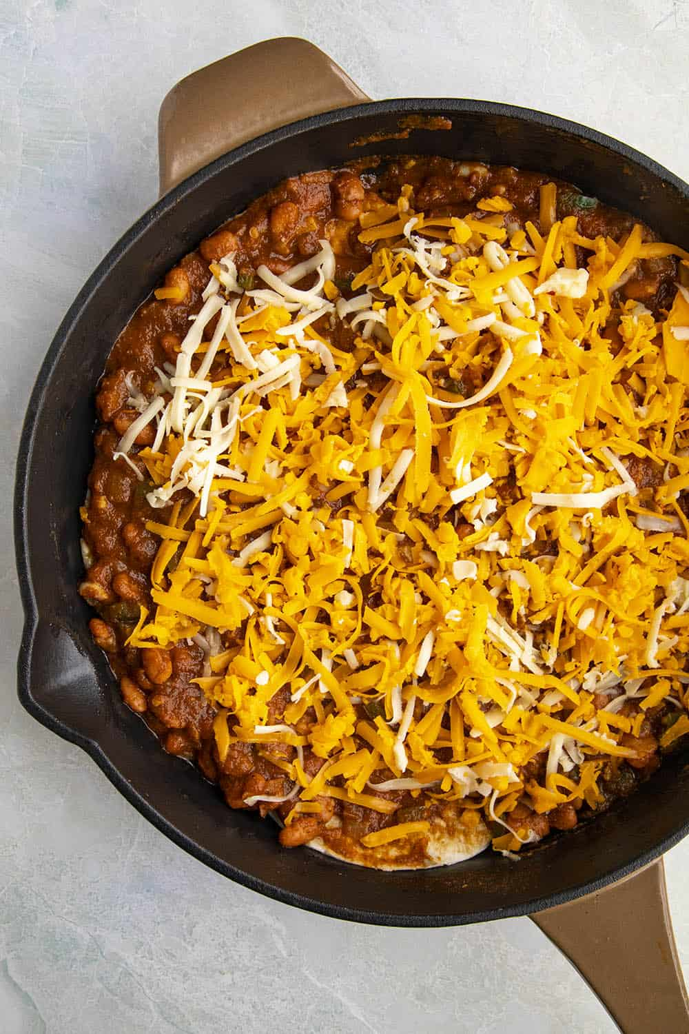 Topping the Huevos Ranchers Casserole with lots of shredded cheese