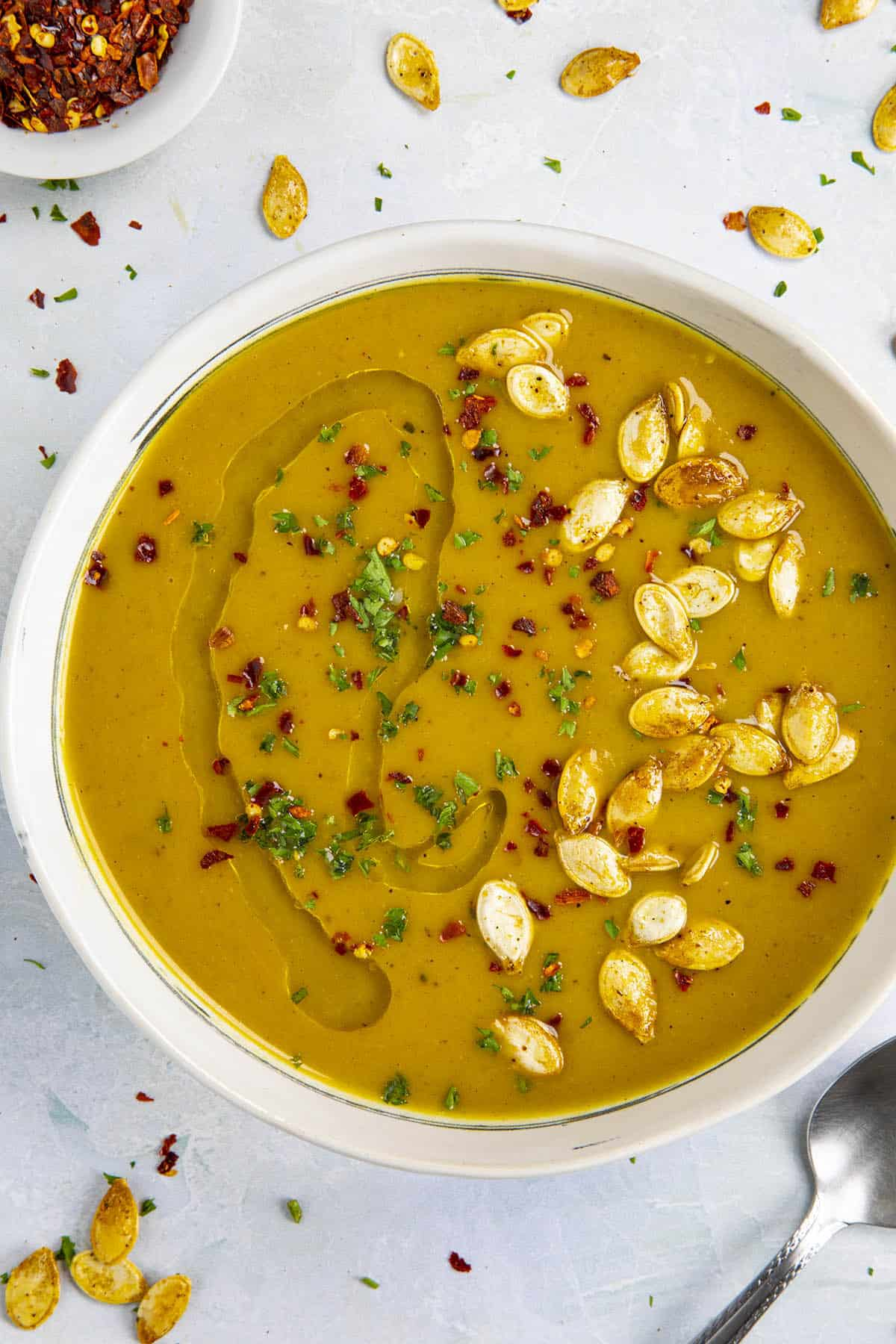 Spicy Pumpkin Soup in a bowl with pumpkin seeds and olive oil swirled over the top