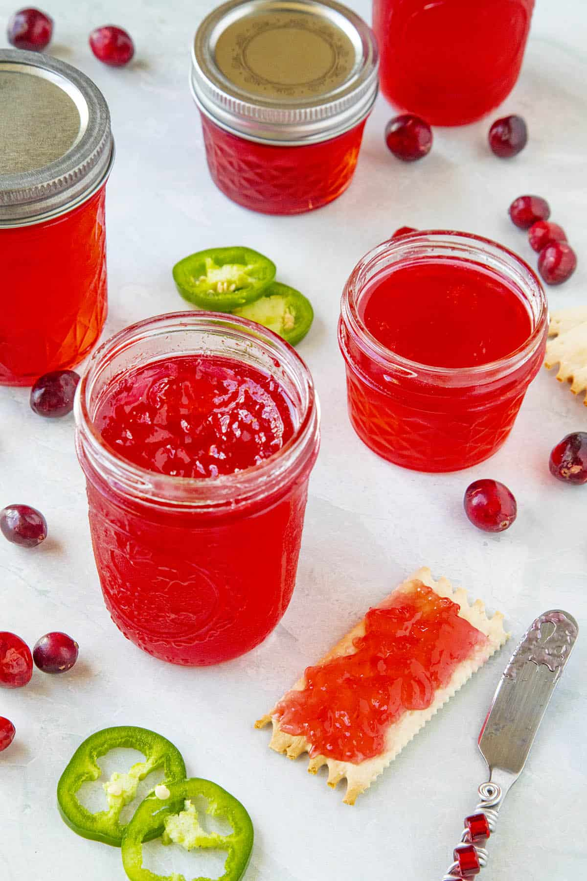 Cranberry Jalapeno Jelly in jars and spread onto a cracker