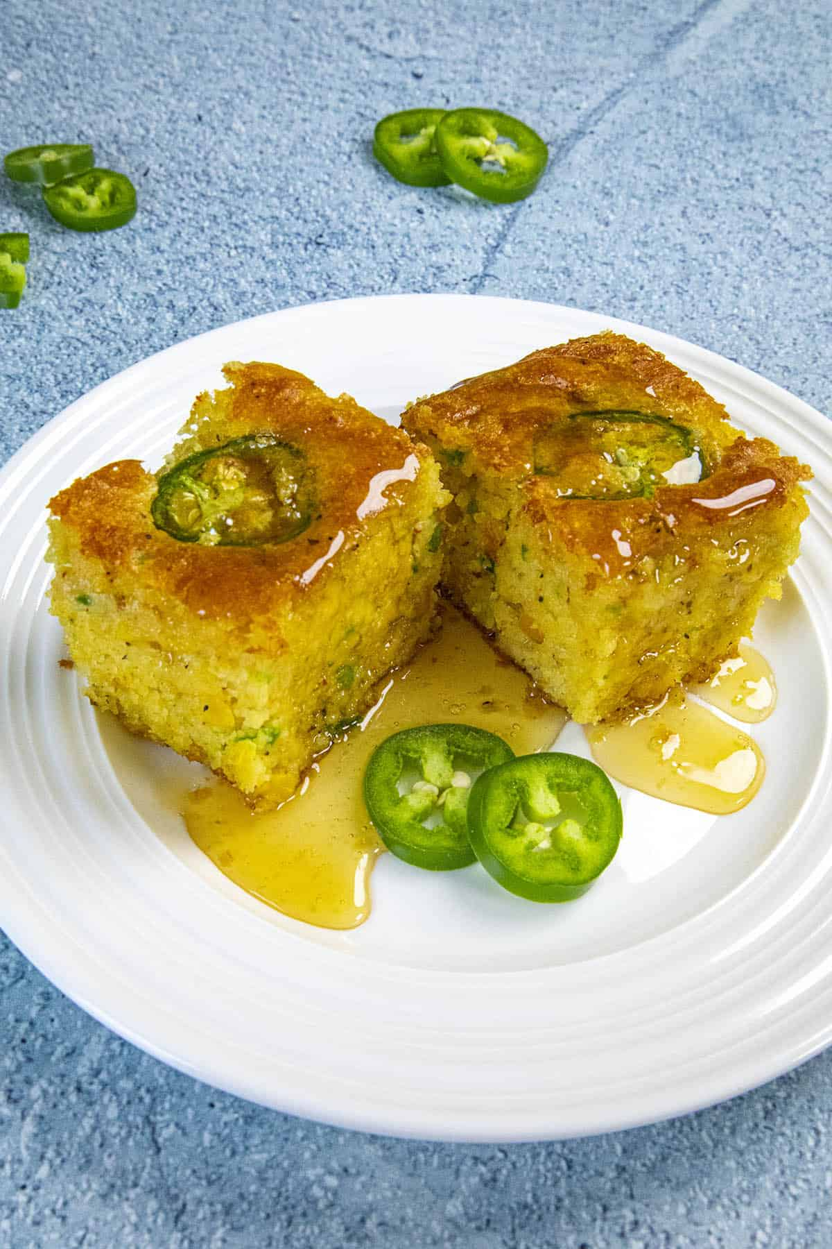 Two slices of Jalapeno Cornbread dripping with honey