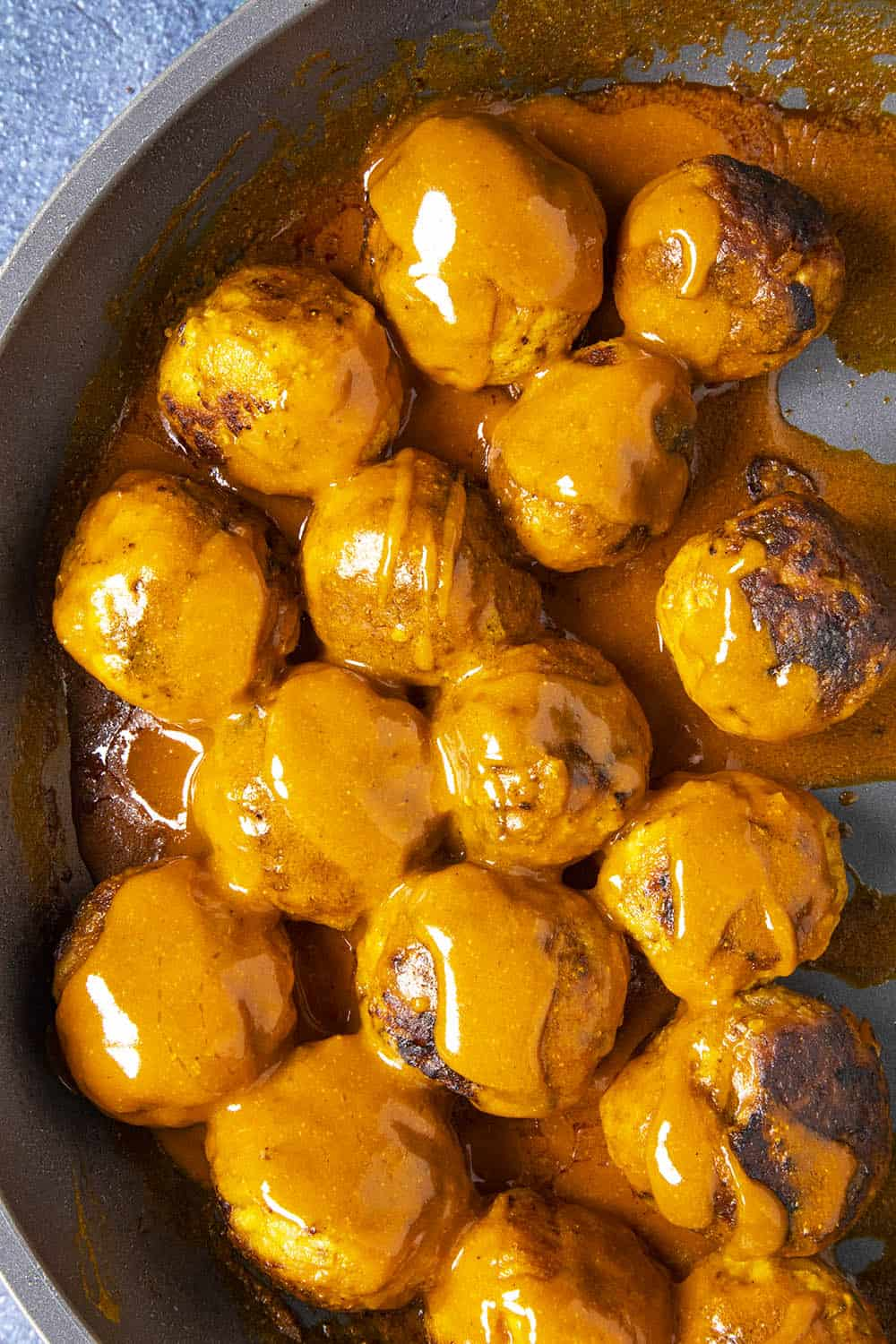 Buffalo Chicken Meatballs in a pan with extra Buffalo sauce