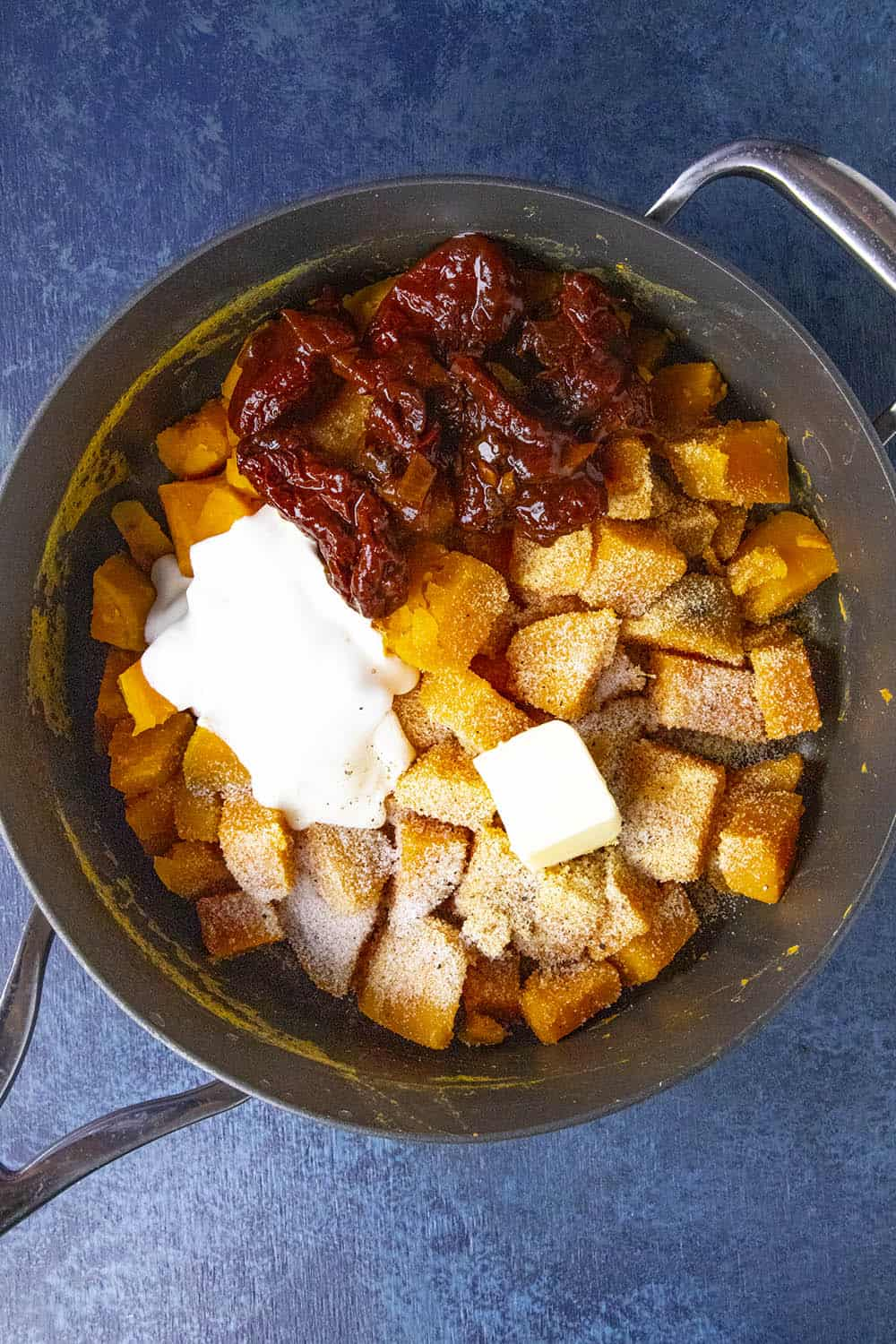 Boiled sweet potatoes in a pot with chipotles, crema, butter and seasonings, ready to mash