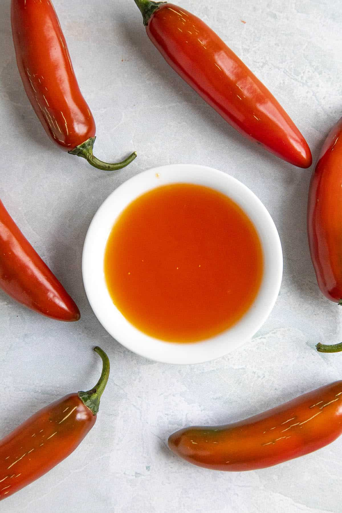 Red Serrano Hot Sauce in a small bowl, surrounded by red serrano peppers