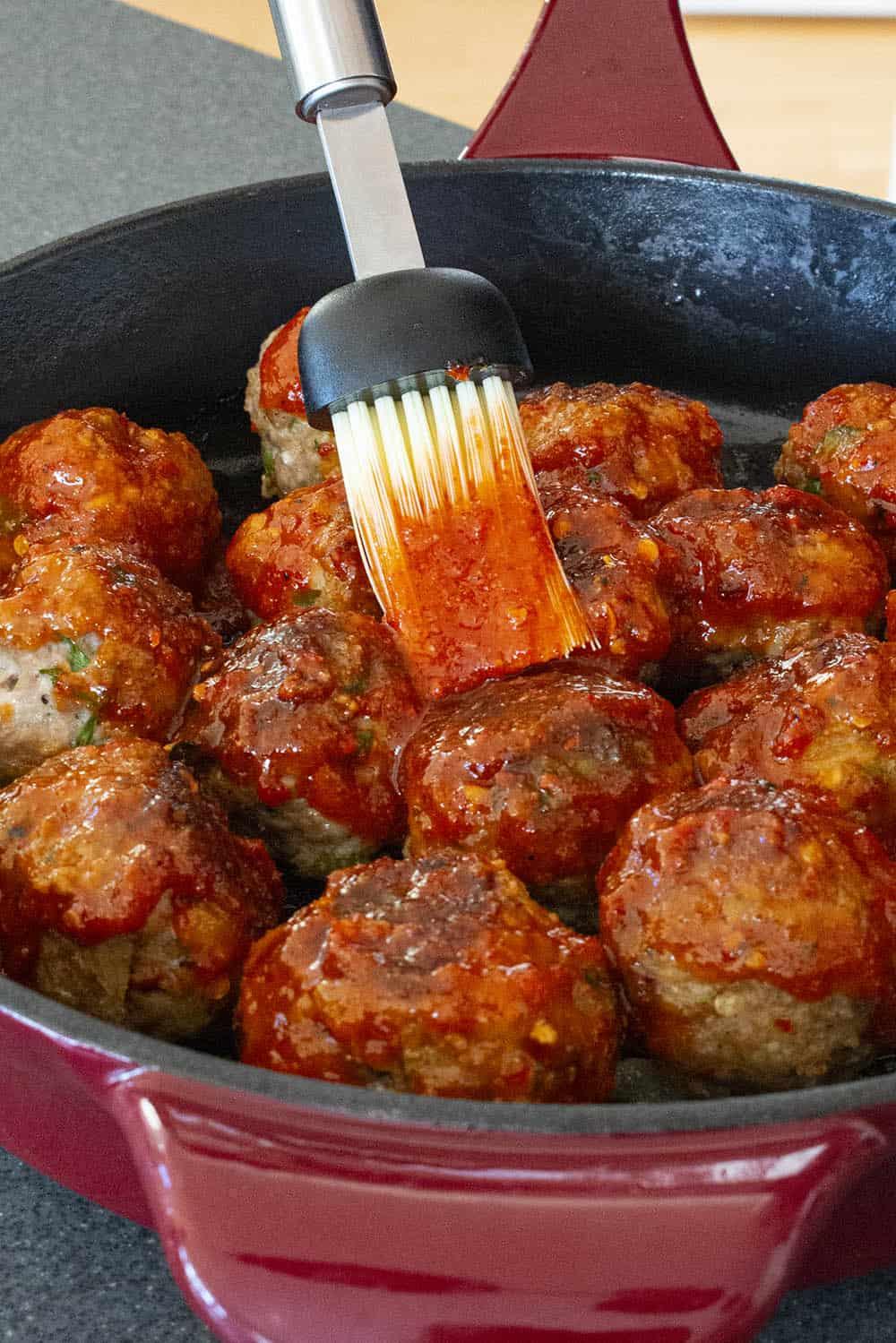Brushing the honey-sriracha glaze over the turkey meatballs