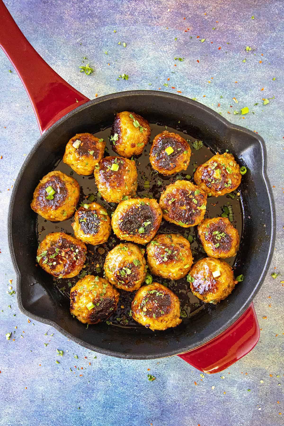 Spicy Korean Chicken Meatballs in a pan, glistening with sticky gochujang glaze